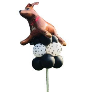 Large dog on top of paw print balloons stuck on a pole for yard display